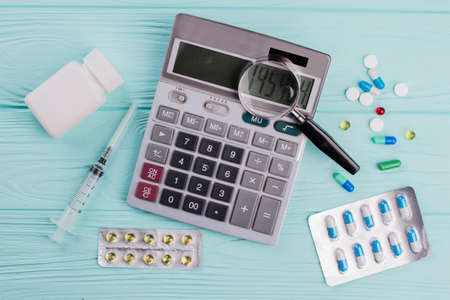 Stethoscope and magnifier over a calculator symbol for health care costs or medical insurance. Health care costs.
