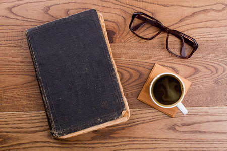 Old book with cup of coffee and glasses. Topview flat lay. Brown wooden background.