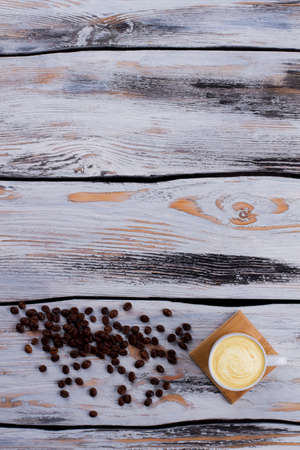 Cup of coffee with foam and coffee beans. White wooden background.