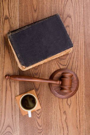 Judges hammer with old book and cup of coffee. Auction Or Trial Or Law Education Concept. Brown wood on background.