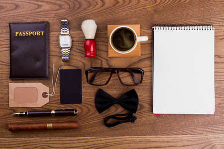 Flat lay morning notepad and men's accessories. Glasses, passport, watch and cup of coffee. Brown wooden table on background.