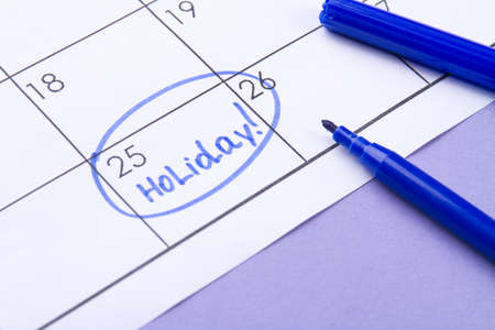 Calendar and holiday concept. 25 day of the month marked as a holiday by a blue felt-tip pen.