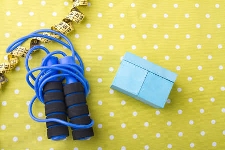 Skipping rope with measuring tape and cupboard on dotted yellow background. Flat lay composition. Reklamní fotografie