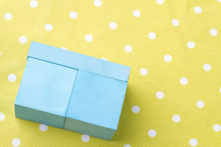 Small blue wooden box. Yellow dotted background. Reklamní fotografie