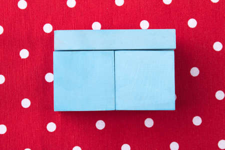 Unusual gift box. Small blue box on red dotted background. Stok Fotoğraf