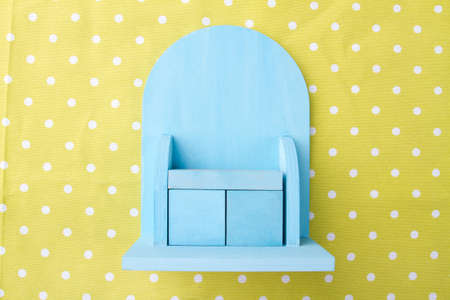 Miniature blue cupboard on dotted yellow background. Small toy furniture. Flat lay photo.