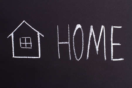 Home word on a black chalk board. Dreaming of buying a house. Stock Photo