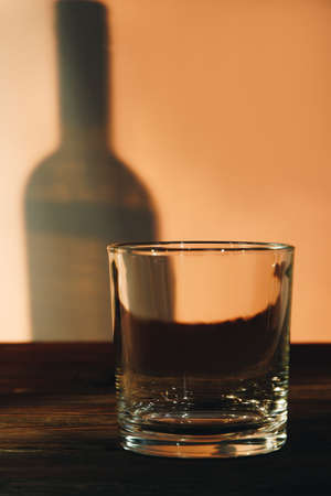 Clean empty whiskey glass and shadow of bottle. Crystal glass with reflection. Concept of alcoholism.