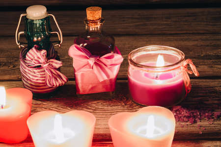 Beautiful romantic pink candles with aroma bottles on wooden background. Arrangement of stuff for spa therapy procedure. Stok Fotoğraf