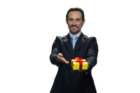 Attractive boss handing a present. Happy mature man in suit isolated on white background.
