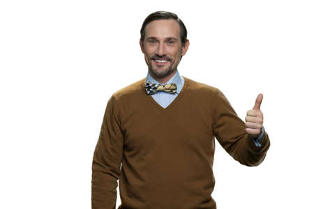 Positive middle-aged man in browm sweater with bowtie. Caucasian casual-dressed man isolated on white background.