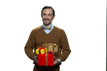 Smiling mature man is holding a pile of gifts. Handsome adult male in brown sweater isolated on white background.