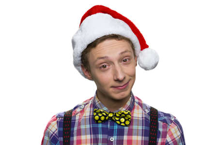 Portrait of european teenage boy with arrogant facial expression. Wearing christmas hat. Isolated on white background.