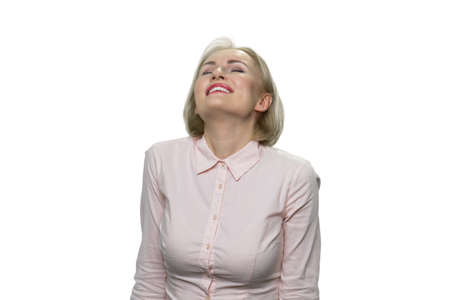 Pleasured and relaxed mature woman with her eyes closed. Blond middle-aged woman wearing shirt is looking up. Isolated on white background.