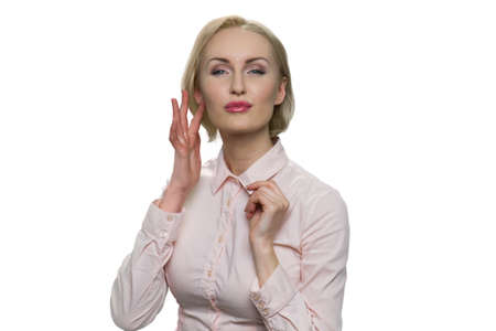 Confident beautiful blond woman in white blouse against white background. Girl holding hand near face.