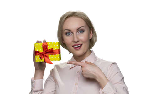 Happy surprised blond woman holding little present box in her one hand. Excited cute girl.