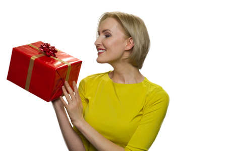 Admired blonde woman holding and looking atpresent box on white background. Receiving gifts from.