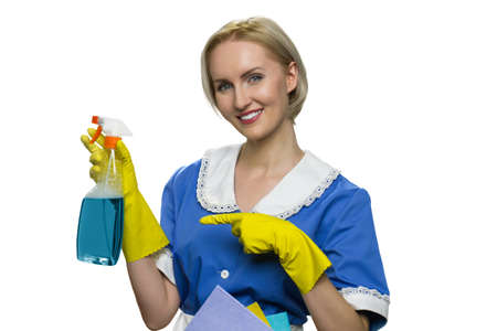 Housekeeper in uniform, yellow rubber gloves spray on white background. Smiling maid pointing at bottle of spray. Stock Photo