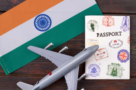Flat lay concept of flight to India. Top view airplane model with flag of India and travel passport on wooden table.
