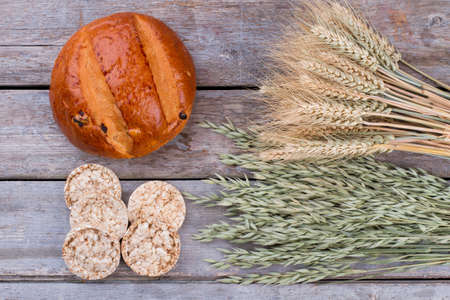 Baked bread, crispbread and weat ears. Tasty bun, crisp bread and cereal spikelets on wooden background. Organic food concept.