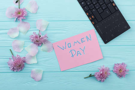 Women day in office flat lay. Pc keybpard with fmany flowers on a blue wooden table. Reklamní fotografie