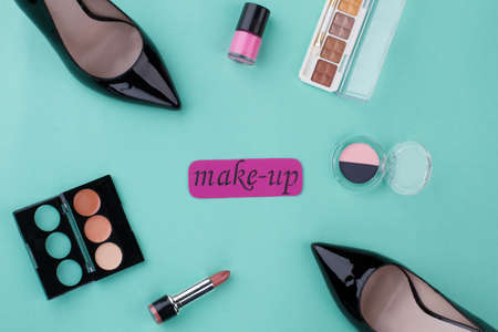 Make-up accessories and female shoes. Top view flay lay. Isolated on turquoise background.
