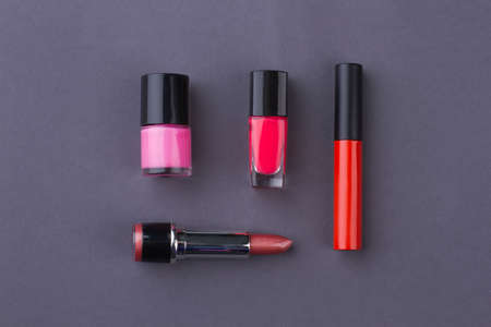 Set of layout accessories on grey background. Lipstic with mascara and lacquer.