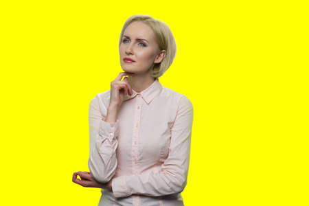 Beautiful young business woman with thoughtful expression. Pensive business lady with hand under chin on color background.