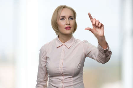 Business woman using an invisible virtual screen. Attractive woman zooming with fingers an icon on a virtual screen.