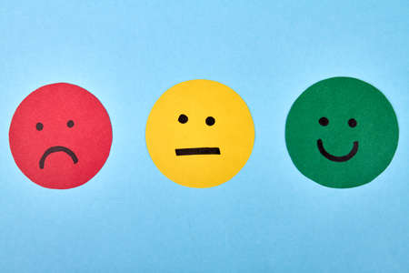 Three emoji with different expressions. Negative, neutral and positive smiliey faces isolated on blue background.
