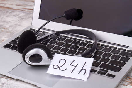 Concept of 24/7 hotline. Headset with laptop of helpdesk support employee.