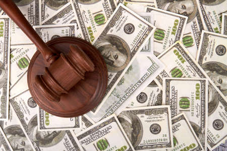 Judge hummer on dollars bacground. Judicial corruption concept. Wooden hammer and banknotes background.