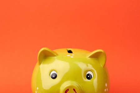 Ceramic yellow piggy bank. Saving money concept. Shiny piggy bank isolated on orange background.