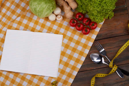 Top view opened copy book with vegetables. Food, spoon, fork and measure tape on wooden table. Diet plan concept.
