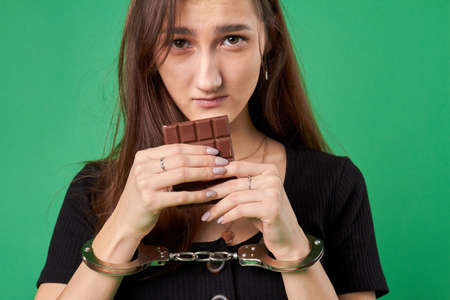 Girl in handcuffs is holding chocolate. Breaking diet concept. Close-up portrait of young woman with chocolate isolated on green background.