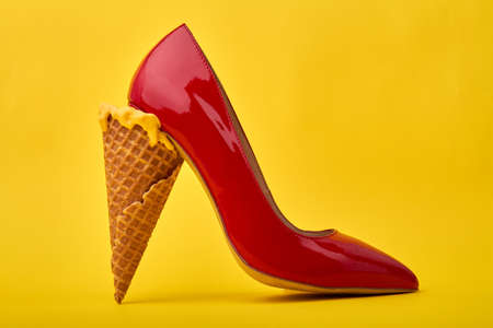 Ice cream cones used as a high heel. Original footwear design concept. Isolated on yellow background. Banco de Imagens