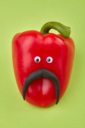 Red bell pepper with eyes and mustache. Head of funny bell pepper isolated on green background.