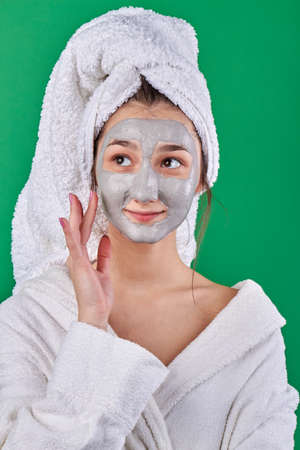Portrait of young girl with skincare mask. Womans wearing bathrobe and towel on her head. Health and spa treatment.