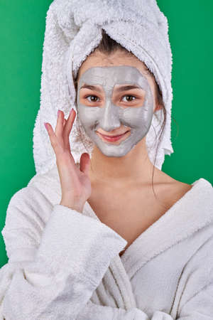 Smiling young woman with healing face mask. Girl wearing bathrobe and applying moisturizing cream. Stock Photo