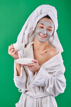 Portrait of girl enjoying tea during spa treatment. Young woman with cream facial mask wearing bathrobe and towel on her head. Isoalted on green background. Stock Photo