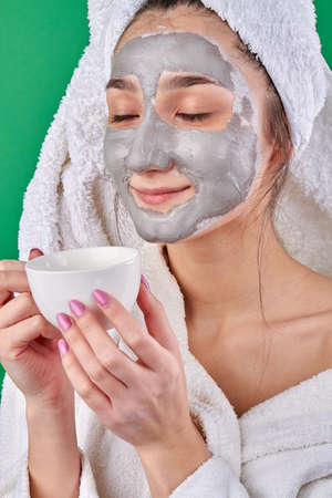 Close-up portrait girl with clay facial mask enjoying tea. Young cute woman drinking aromatic tea during spa treatment.