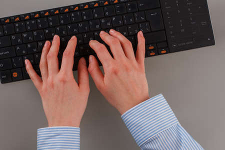 Close up female hands working on computer keyboard. Business woman hands typing on black computer keyboard. Stock Photo
