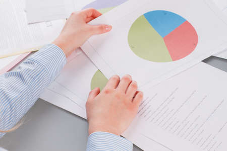 Human hands holding business documents. Documents with graphs and charts on the table at office.
