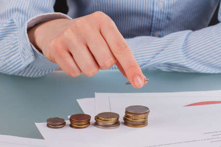 Business woman stacking coins on table for saving money. Financial freedom concept.