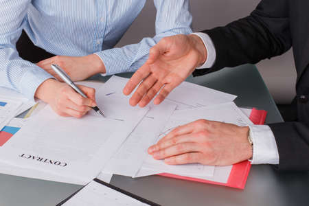 Woman client putting signature on legal document. Female hand puts signature on business document making employment contract agreement. Investment or insurance deal after successful negotiation.