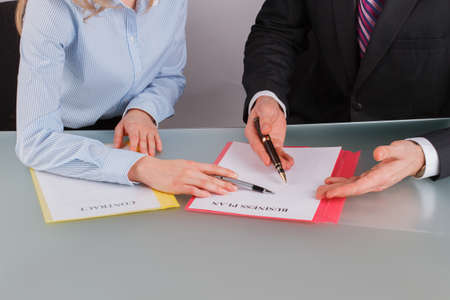 Businessman and businesswoman working with documents close up. Business people discussing advantages and disadvantages of business plan. Future partnership and cooperation.
