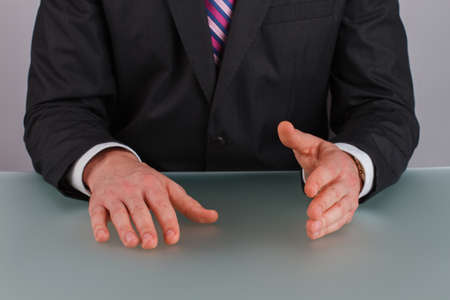 Confident businessman sitting at table. Gesturing hands of business person or politician. Business solution concept.