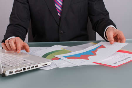 Close up view of businessman working with laptop and documents at office. Male accountant reviewing his business graphs. Stock exchange market.