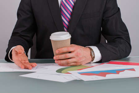 Business advisor analyzing company financial report. Businessman holding disposable coffee cup while working with documents at desk in office.