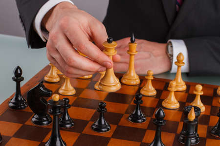Close up businessman hand playing chess. Wooden chess board with chess figures and male hands. Business, leadership and strategy concept.